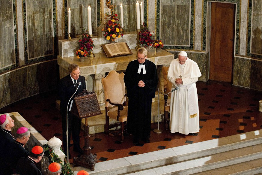 November 15 2015 : Pope Francis flanked by Rev. Jens-Martin Kruse, prays during a visit to the Lutheran church, in Rome, Italy.